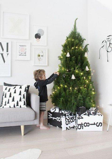 Небольшая елка в углу детской украшенная светящейся гирляндой и глиняными елочными игрушками.