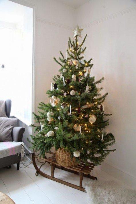 Оригинальная елка в корзине на  деревянных санях украшенная помпонами и свечками.