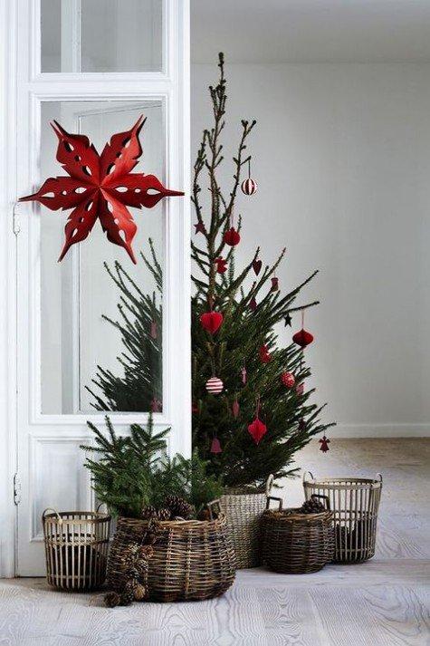 Скромная елка в корзине украшенная красными игрушками. У елки стоят корзинки поменьше с хвоей и шишками. Окно украшено рождественской звездой из красной бумаги.