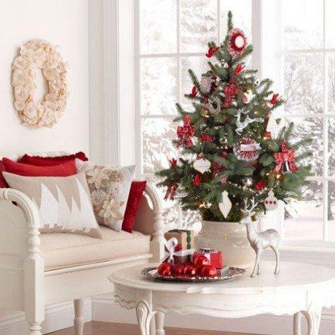 Традиционно украшенная елка в горшке на журнальном столике.