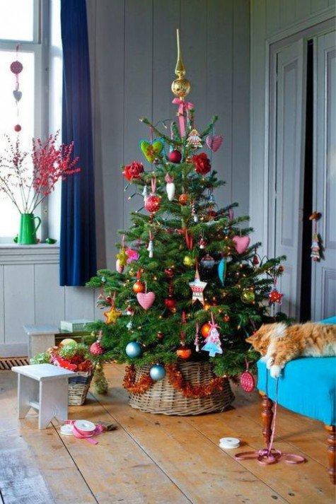 Яркая елка в корзине украшенная разноцветными елочными игрушками, звездами, цветами и сердечками.