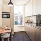 Кухня расширяется к окну, а кухонная столешница, соответственно, сужается до расстояния между стеной и окном. Кухонный стол сварен из профильной трубы и хорошо сочетается со стальным фасадом нижних шкафов кухни.