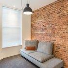 Серый диванчик напротив телевизора. Одна стена в гостиной отделена красным кирпичом. (индустриальный,лофт,винтаж,стиль лофт,индустриальный стиль,квартиры,апартаменты,мебель,интерьер,дизайн интерьера,современный,гостиная,дизайн гостиной,интерьер гостиной,мебель для гостиной,фото гостиной,идеи гостиной)