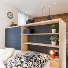 Спальня на подиуме скрыта от гостиной стеллажом. В нем расположены полочки для книг, будильника и прочих вещей.