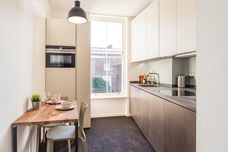Кухня расширяется к окну, а кухонная столешница, соответственно, сужается до расстояния между стеной и окном. Кухонный стол сварен из профильной трубы и хорошо сочетается со стальным фасадом нижних шкафов кухни