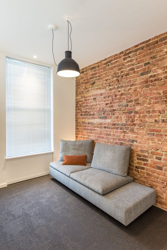 Серый диванчик напротив телевизора. Одна стена в гостиной отделена красным кирпичом.