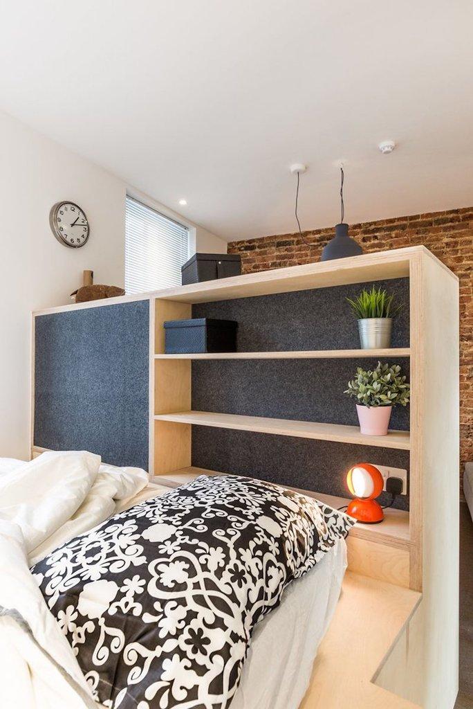 Спальня на подиуме скрыта от гостиной стеллажом. В нем расположены полочки для книг, будильника и прочих вещей