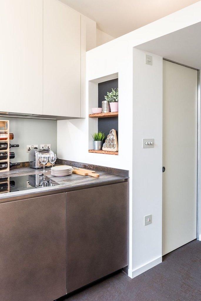 Стальной нижний кухонный фасад и нейтральный верхний выглядят современно и не уменьшают кухню визуально. Над ванной хорошо видна антресоль для хранения мелочей.