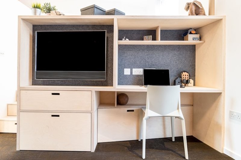 В стеллаже отделяющем гостиную от спальни разместили телевизор и домашний офис