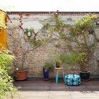 Озелененная терраса с заплетенной плющем кирпичной стеной напоминает небольшой дворик.