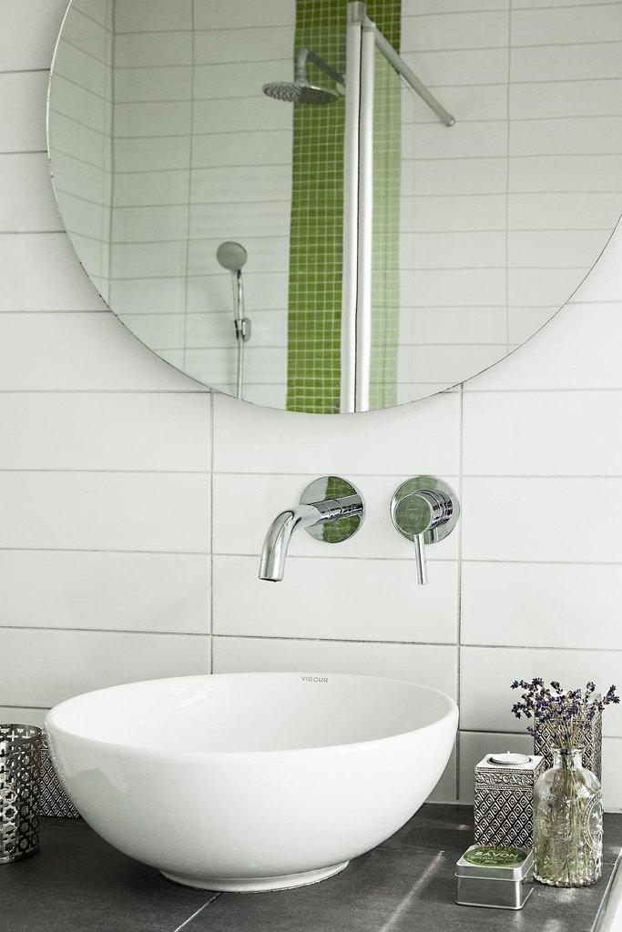 Светлая ванная комната с зелеными и серыми акцентами в отделке.