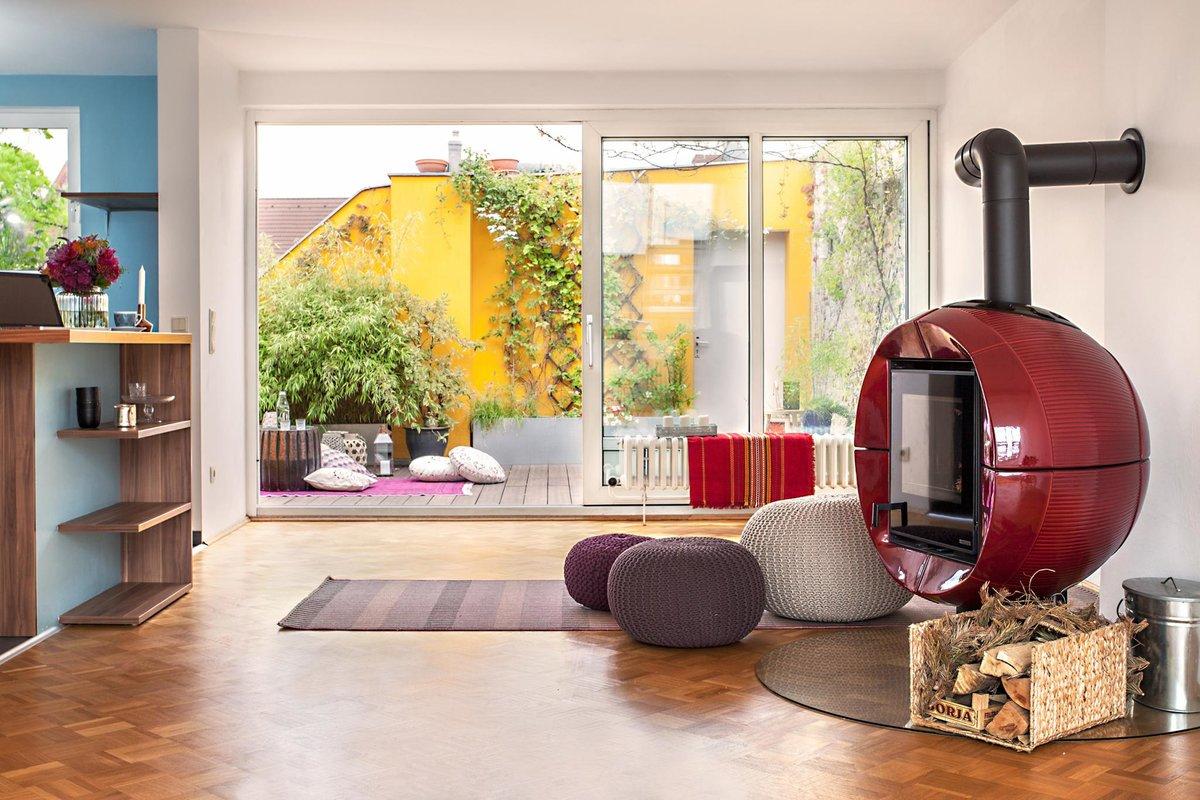 В центре гостиной расположен красный поворотный камин. На террасу выходит большое раздвижное окно от пола до потолка.