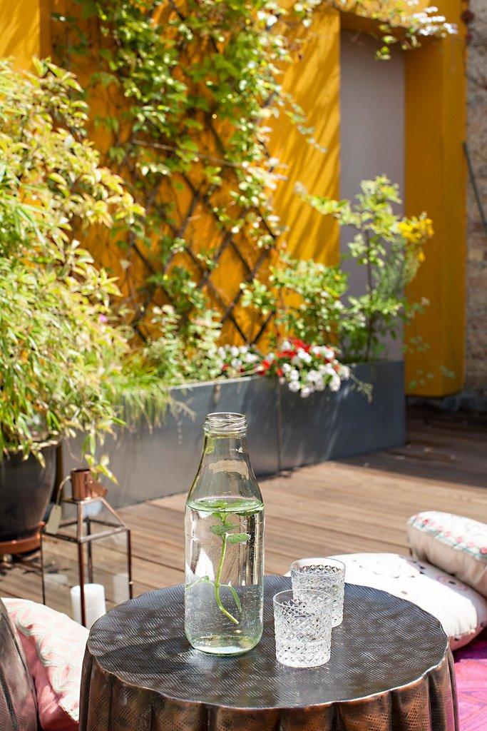 Вдоль стен террасы расположены ящики для цветов и зеленых растений.