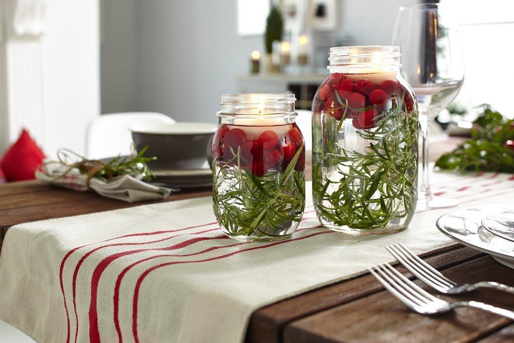 Красная клюква цвета Рождества в банке с веточками розмарина и плавающими свечками могут украсить рождественский стол.