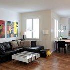 В жилой комнате у окна расположен круглый обеденный стол, а за углом черный кожаный угловой диван гостиной. На стене над диваном две яркие картины.