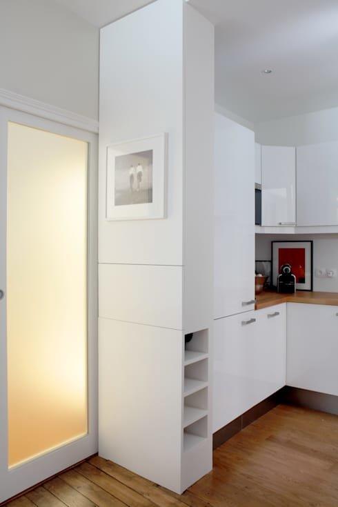 Белую кухню украшают картины на кухонной столешнице и боковой стене кухонной мебели рядом с дверью на балкон