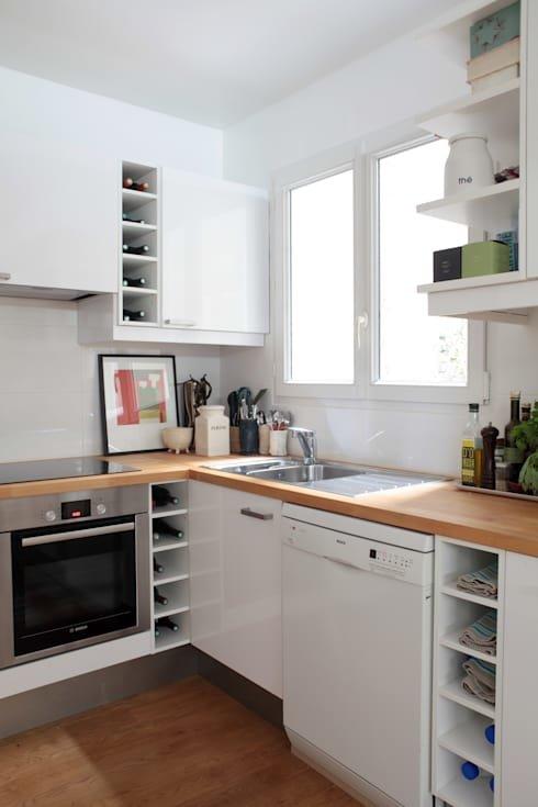 Деревянный пол с деревянным столом смягчают холодный белый интерьер. Картина на кухонной столешнице делает интерьер кухни еще приятнее