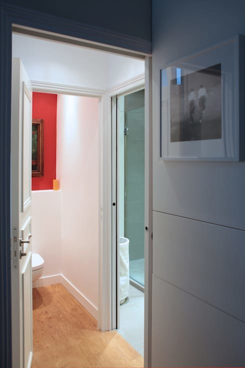 Санузел в квартире раздельный. В туалете хорошо заметна акцентная красная стена за унитазом с картиной в классической раме.