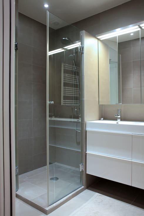 Серая современная душевая находится рядом с туалетом. Тут явно недостает некоторого декора. Яркие полотенца и прочие аксессуары безусловно оживят помещение.