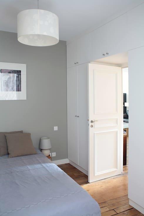 Спокойный интерьер спальни в серых тонах. Белый плательный шкаф занимает всю стену и мало заметен