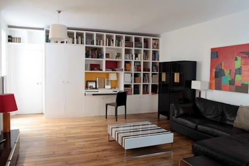В гостиной шкаф и полки занимают целую стену от пола до потолка. В этой же мебельной стенке предусмотрено рабочее место домашнего офиса.