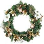 Хвойный венок украшенный традиционным елочным декором - цветами, листиками и шарами.