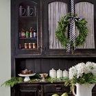Хвойный венок закрепленный на широкой полосатой ленте украшает кухонную мебель.