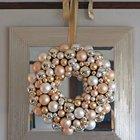 Пышный рождественский венок из елочных шаров на фоне зеркала.