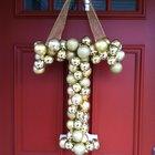 Рождественский венок из елочных игрушек на двери дома в виде монограммы.