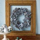 Рождественский венок из подкрашенных белой краской шишек в деревянной раме.