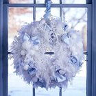 Рождественский венок из снежинок, белых шерстяных шариков и лент украшает окно.