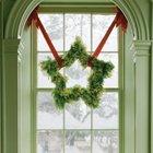 Рождественский венок в форме звезды закрепленный на красных лентах в оконном проеме.