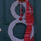 Венки из белой крашенной виноградной лозы в виде снеговика в котелке и с красным шарфом на входной двери.