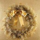 Венок из белых веточек хвои украшенных золотистыми игрушками и бантом.