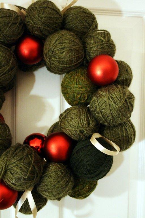 Необычный рождественский венок из моточков зеленой шерсти и красных елочных шариков.