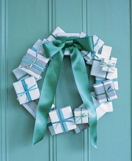 Рождественский венок из маленьких подарочных коробочек с бирюзовым бантом украшает зеленую дверь.