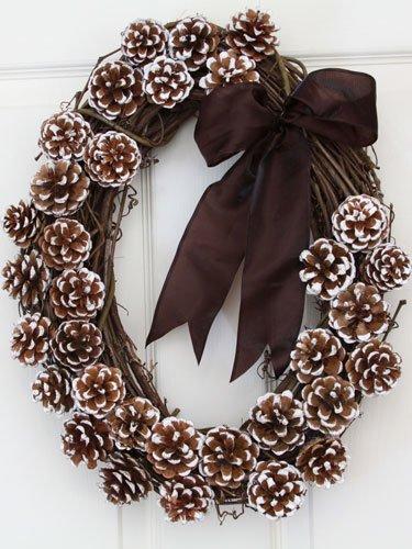 Рождественский венок в коричневых тонах из виноградной лозы, подкрашенных шишек и коричневым бантом.