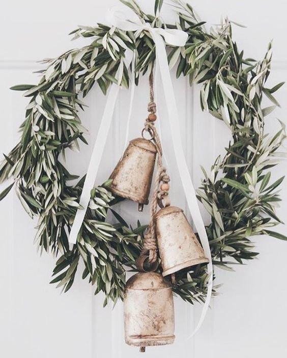 Рустикальный венок из оливковых ветвей с колокольчиками и бантом из белой ленты.