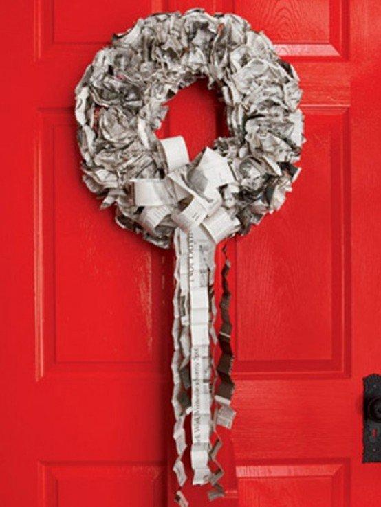 Серебристый венок из газет на красной двери.
