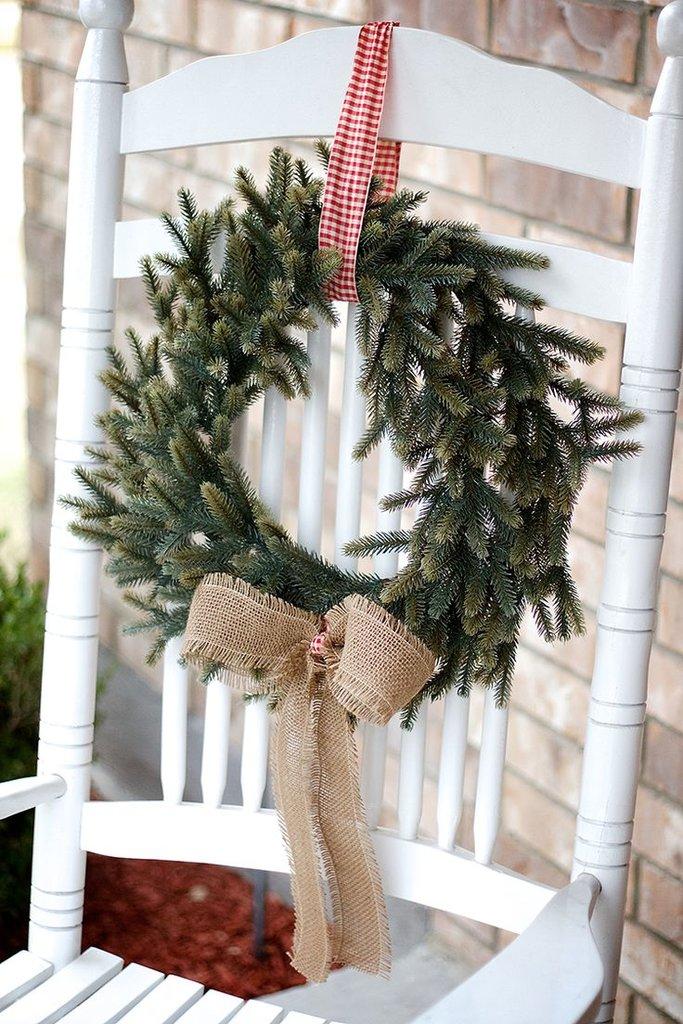 Скромный рождественский венок из елочных веточек с бантом из мешковины.