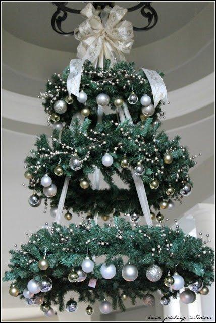 Три горизонтальных венка из хвои украшенные елочными игрушками по форме образуют елку.