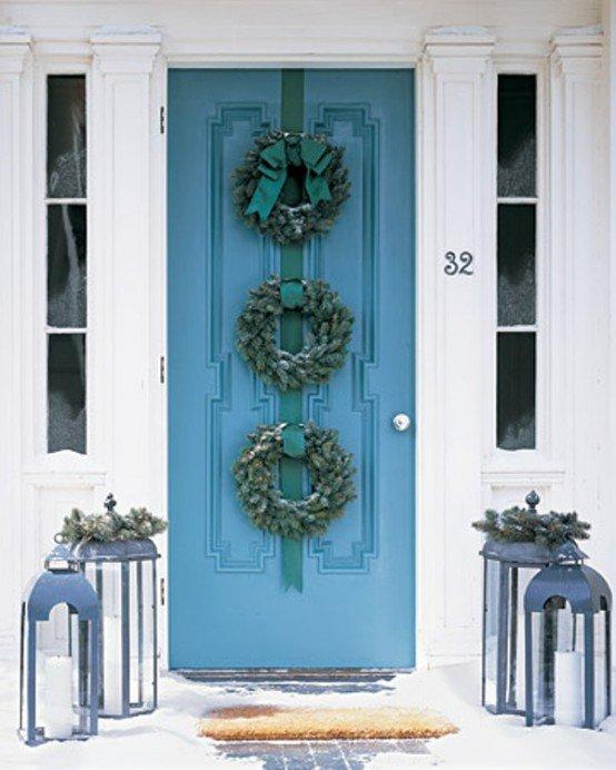 Три венка из хвои закрепленные на зеленой ленте украшают входную дверь снизу до верху.