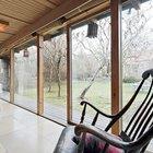 Остекленная южная стена жилой комнаты впускает окружающую дом природу и зелень внутрь в интерьер дома.