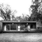Остекленный южный фасад дома. В центре дома заметен камин разделяющий гостиную со столовой.