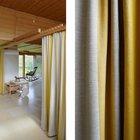 Плотные шторы служат разделителями жилой комнаты.