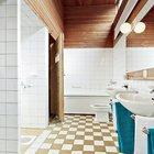 Ванну украшает отделка деревом тика и большое зеркало во всю стену.Легко заметить приоткрытую дверь в сауну.