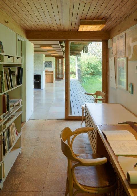 Домашний офис в торце террасы со стеллажами и рабочим столом. Пол в кабинете из пробковых панелей