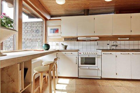 Кухня окнами выходит во двор с северной стороны дома. Вдоль окна проходит массивная столешница служащая барной стойкой.