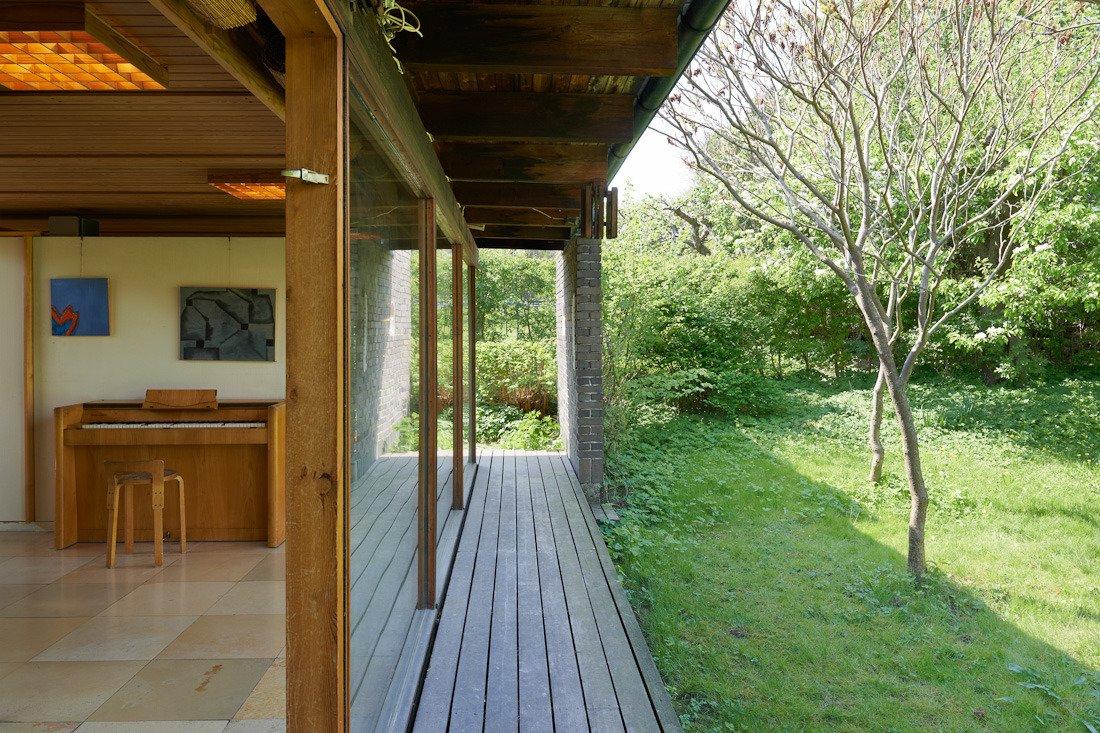 Узкая терраса с широким свесом крыши защищает южный фасад дома от летнего солнца.
