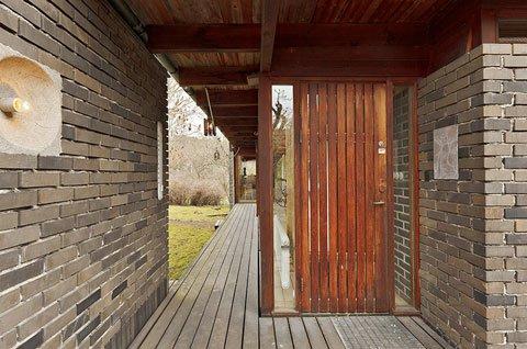 Узкая терраса вдоль жилой комнаты и главный вход в дом.